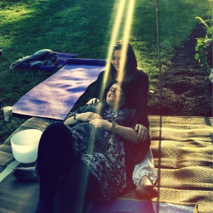 Two women practicing Reiki in an outdoor environment.